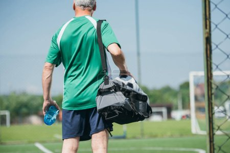 back view of old man with sportive water bottle and bag on soccer field