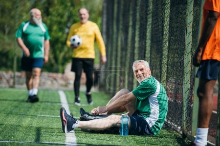 selective focus of interracial elderly football players after match on green field