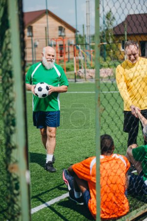 interracial elderly football players shaking hands after match on green field