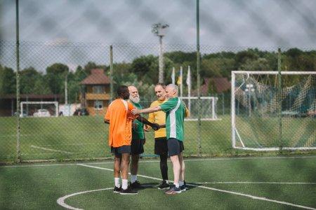 interracial elderly football players after match on green field