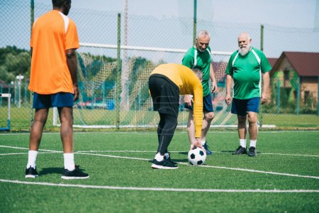 multicultural elderly friends playing football together