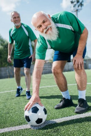 selective focus of elderly beaded men in football uniform with football ball on green field