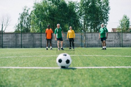 selective focus of football ball and multicultural elderly men on green football field