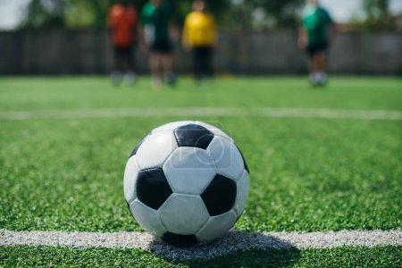 Photo for Selective focus of football ball and players on green football field - Royalty Free Image