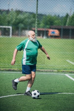 elderly bearded man playing football on field on summer day