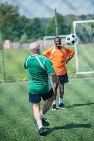multiracial old men playing football together on green field