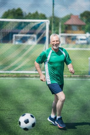 cheerful old man playing football on field on summer day