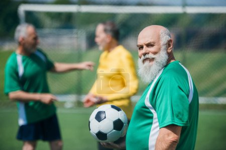 selective focus of old bearded man with football ball and friends behind on field