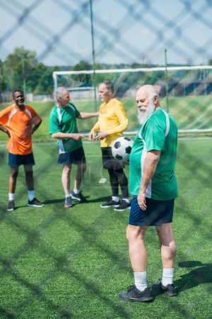 selective focus of multiracial old friends with football ball on green field
