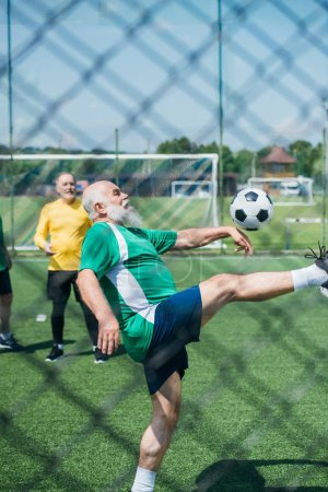 partial view of elderly men playing football on field