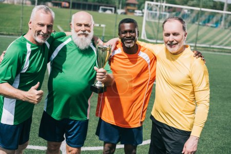 multiethnic smiling old sportsmen with champions cup standing on football field