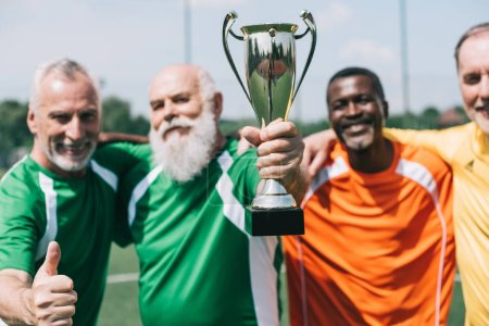 selective focus of multiethnic smiling old sportsmen with champions cup standing on football field