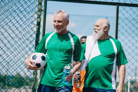 multicultural smiling elderly men with sportive water bottles and football ball