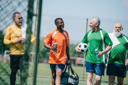 group of interracial elderly sportsmen with sportive water bottles walking on football field