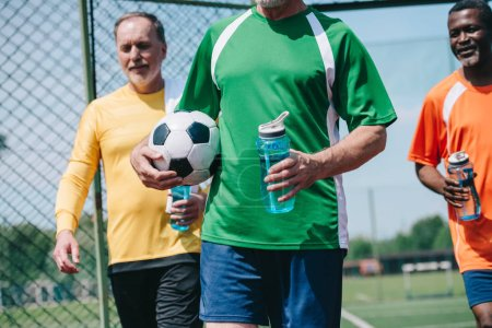partial view of multicultural elderly men with sportive water bottles and football ball