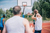 selective focus of interracial elderly sportsmen playing basketball together on playground