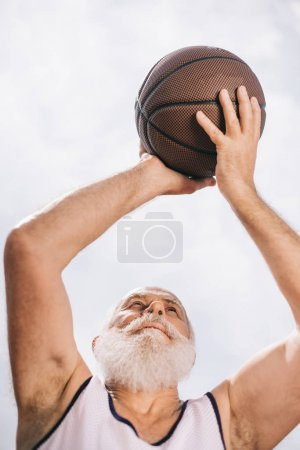 low angle view of elderly bearded man with basketball ball in hands