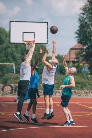 Photo for Interracial elderly sportsmen playing basketball together on playground - Royalty Free Image