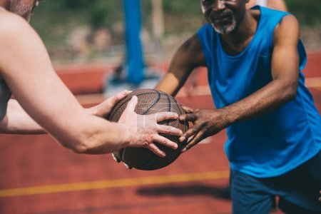 partial view of man giving basketball ball to old african american friend