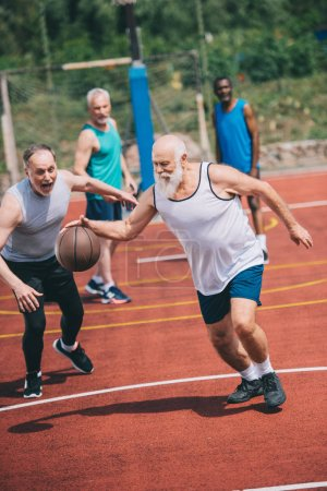 interracial elderly sportsmen playing basketball together on playground