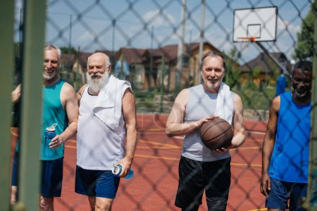 smiling multiethnic elderly sportsmen with basketball ball on playground