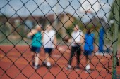selective focus of net and players on basketball playground