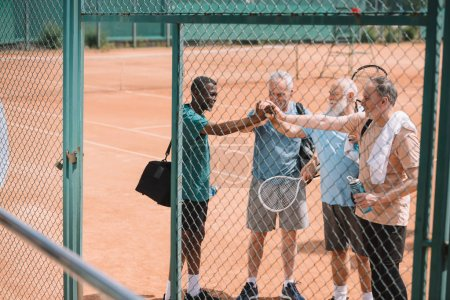 multicultural group of elderly tennis players holding hands together after game on court