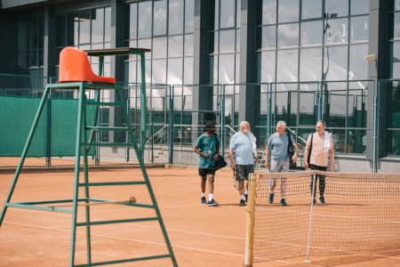 Photo for Multiracial elderly friends with tennis equipment walking on court - Royalty Free Image