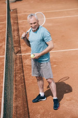 smiling elderly man in sportswear with tennis racquet and ball standing on court