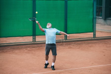 old man playing tennis on court on summer day