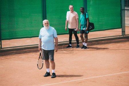 multiracial elderly men standing on tennis court