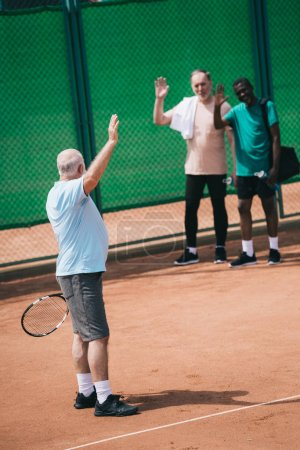 multiethnic old men greeting friend with tennis racquet on court