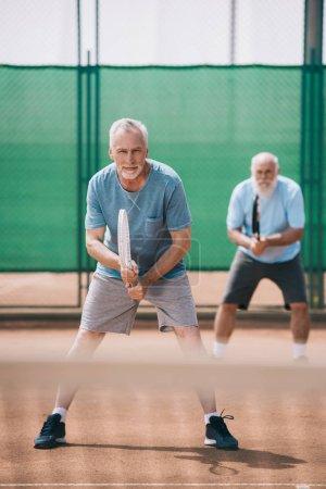 Photo pour Mise au point sélective de vieillards avec des raquettes de tennis sur Cour - image libre de droit