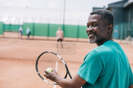 selective focus of smiling elderly african american man playing tennis with friend on court