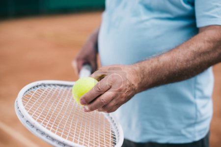 partial view of old man with tennis equipment in hands