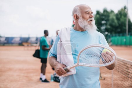 selective focus of bearded old man with towel and tennis racquet on court