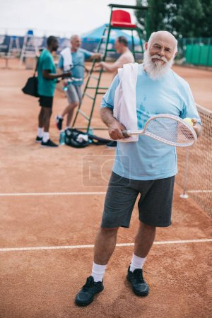 selective focus of elderly bearded man with towel and tennis racquet looking at camera while interracial friends having conversation on court