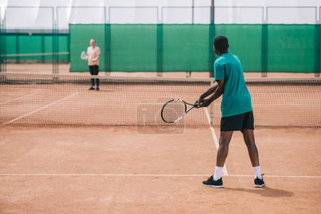 selective focus of elderly african american man playing tennis with friend on court