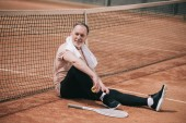smiling elderly man with towel and tennis equipment resting near net on tennis court