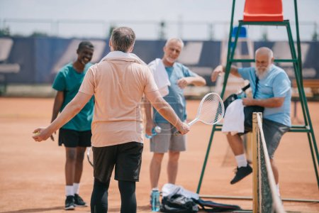 Photo for Selective focus of old multiethnic friends on tennis court on summer day - Royalty Free Image