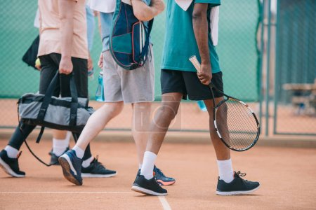 partial view of multicultural elderly men with tennis equipment walking on court