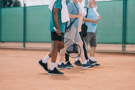 Photo for Partial view of multicultural elderly men with tennis equipment walking on court - Royalty Free Image