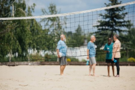 selective focus of net and interracial old men with volleyball ball on sandy beach