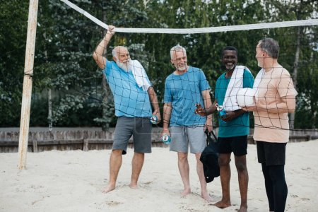 smiling multiracial elderly men with volleyball on sandy beach