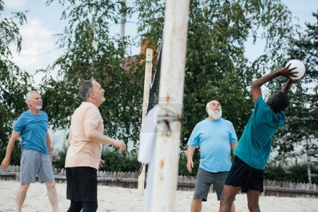 side view of multicultural old friends playing volleyball on beach on summer day