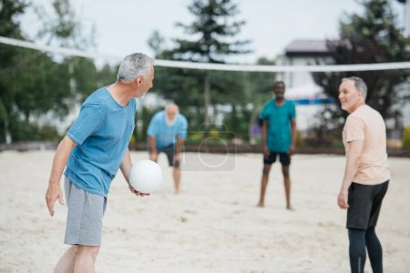 selective focus of multicultural old friends playing volleyball on beach on summer day