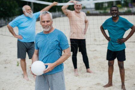 selective focus of multiracial elderly men with volleyball on sandy beach