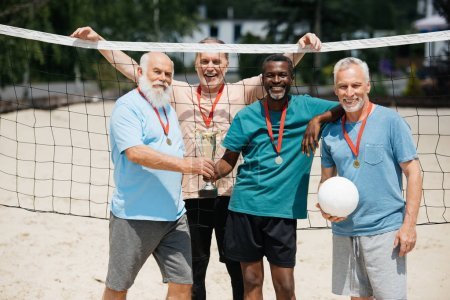 portrait of smiling multiethnic elderly friends with tennis ball, medals and champions cup on beach