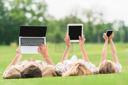 family lying on grass and using digital devices with blank screens