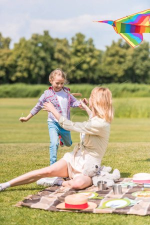 happy mother and daughter spending time together at picnic in park